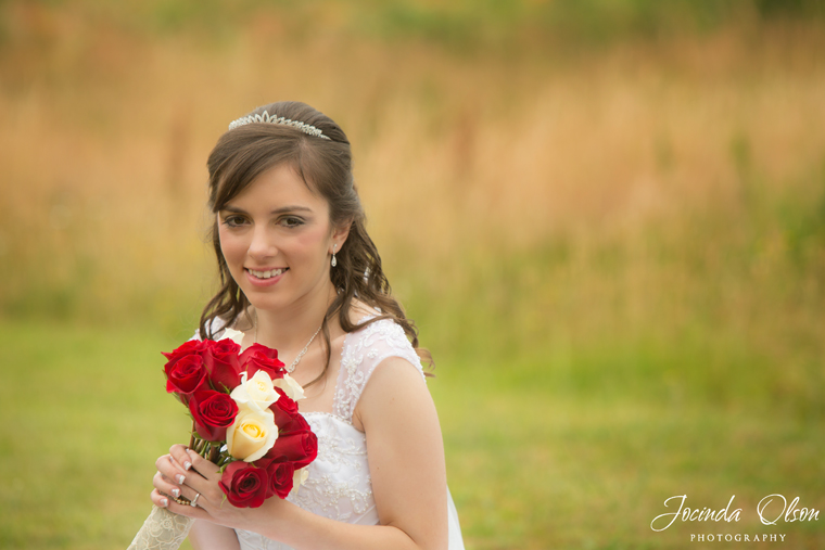 Bride holding red and white roses