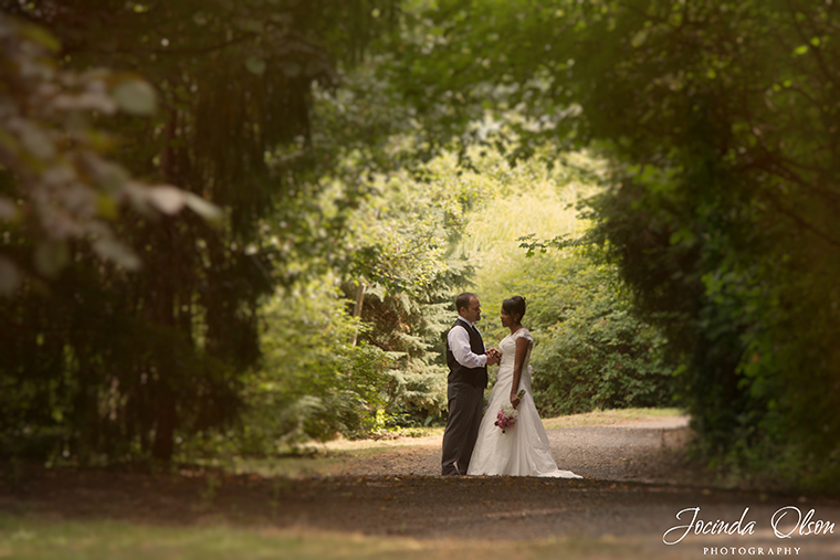 Portrait of Bride and Groom in tunnel of leaves