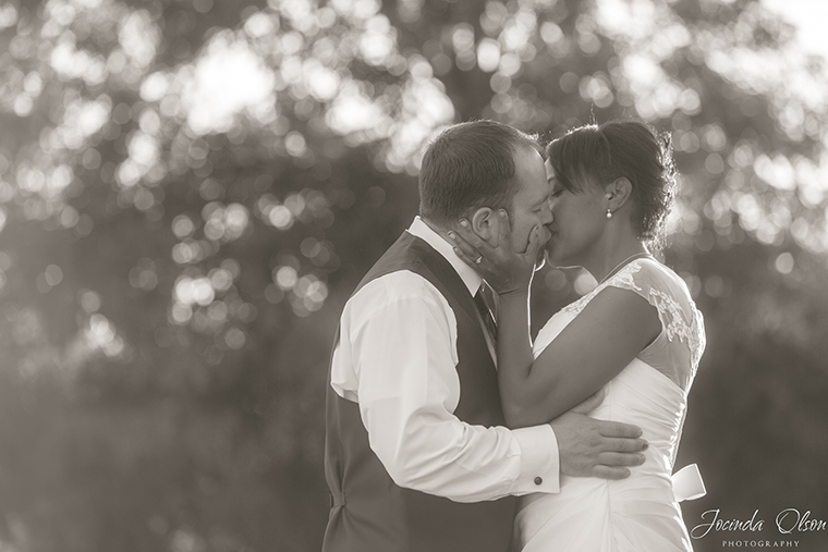 Black and white portrait of bride and groom kissing backlit